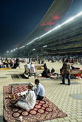 Spectators and grandstand at horse racing meeting at Al Meydan racecourse at night in Dubai United Arab Emirates