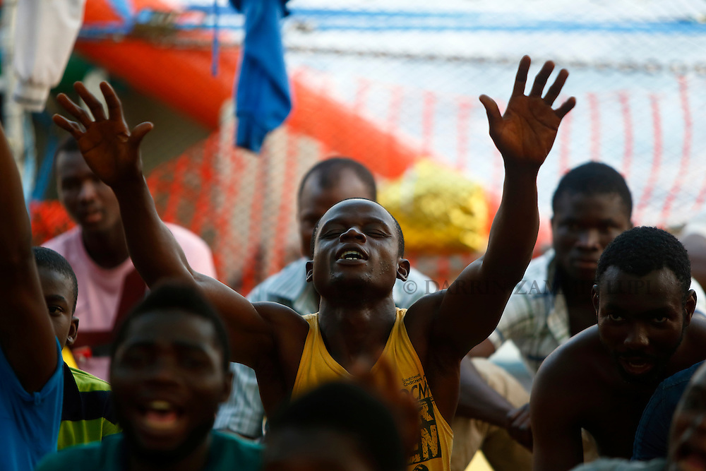Migrants take part in an impromptu prayer meeting at the stern of the Medecins san Frontiere (MSF) rescue ship Bourbon Argos somewhere between Libya and Sicily at sunset August 8, 2015.  Some 241 mostly West African migrants on the ship are expected to arrive on the Italian island of Sicily on Sunday morning, according to MSF.<br /> REUTERS/Darrin Zammit Lupi <br /> MALTA OUT. NO COMMERCIAL OR EDITORIAL SALES IN MALTA