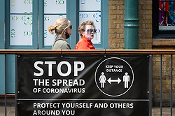 © Licensed to London News Pictures. 08/06/2021. LONDON, UK.  Women pass a Coronavirus warning sign in Covent Garden.  The UK government has announced that over 25s can now receive the coronavirus vaccine. Concerns about the impact of the so-called Indian variant on full relaxation of lockdown restrictions on June 21 continue.  Photo credit: Stephen Chung/LNP