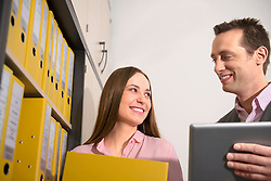 Young couple smiling at each other in office