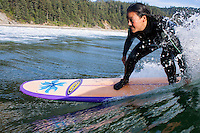Woman surfing at Oswald West State Park, OR.