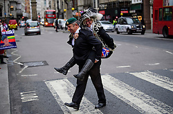 © Licensed to London News Pictures. 21/12/2016. London, UK. A former Royal Marine carries a Pearly Queen on his back across a zebra crossing while arriving to show support at a bail hearing for her husband, Royal Marine Sergeant Alexander Blackman. Sgt Blackman is currently serving a life sentence after being convicted of murdering a wounded Taliban fighter in Afghanistan in 2011. Photo credit: Ben Cawthra/LNP