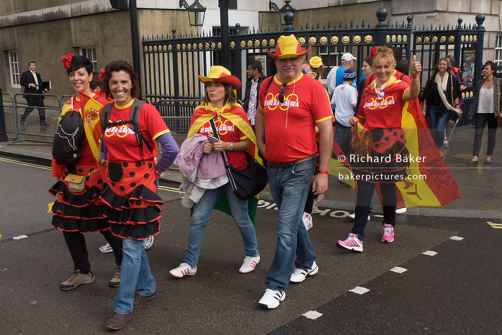 Spanish sports fans tour central London during a break watching events during the London 2012 Olympics. Wearing their country's national colours the friends enjoy a respite from the summer rains to walk through the capital's streets.