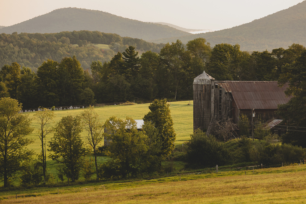 An old barn and silo tucked into the hilly terrain of Vermont's farming landscape.