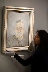 © Licensed to London News Pictures. 01/02/2012. LONDON, UK. A member of Sotherby's staff adjusts Lucian Frued's 'Portrait of a Man' at an auction of Impressionist and Modern Art held on the 8th of February 2012. The painting, never seen before in public, depicts Bernard Walsh, who's Soho restaurant was frequented by artists, including Freud throughout the 1950's and 60's, and is estimated to raise £1,5000,000-2,000,000. Photo credit: Matt Cetti-Roberts/LNP