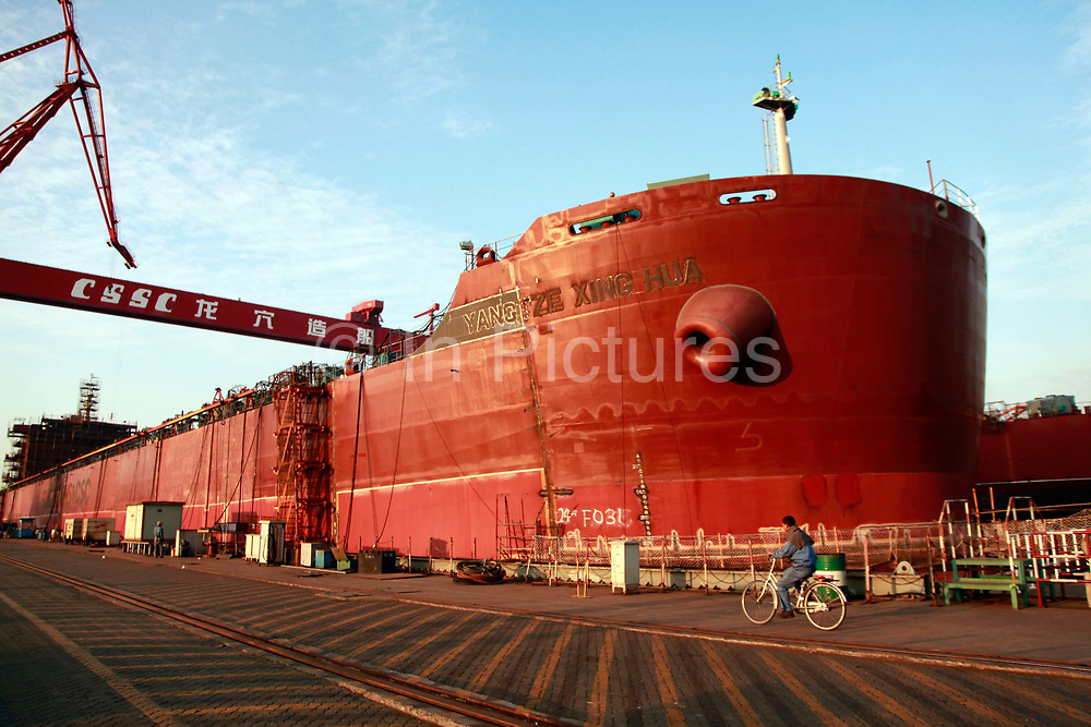 A worker leans over the side of a ship under construction at the China State Shipbuilding Corp.'s (CSSC) Longxue Shipyard in Guangzhou, Guangdong Province, China, on Sunday, Nov. 13, 2011. China is the world's biggest shipbuilder, however recent economic downturns have caused a glut in supplies.