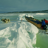 Team drags sled over pressure ridge on frozen Great Slave Lake, NWT, Canada.