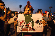 A protestor holds a sketch showing Egyptian president Mohammed Morsi, being forced out of a window by the military in Cairo.