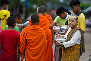 16 SEPTEMBER 2014 - SANGKHLA BURI, KANCHANABURI, THAILAND: A woman pauses after presenting Mon Buddhist monks with food during the morning alms round in the Mon community in Sangkhla Buri. The Mon were some of the first people to settle in Southeast Asia, and were responsible for the spread of Theravada Buddhism in Thailand and  Indochina. The Mon homeland is in southwestern Thailand and southeastern Myanmar (Burma). The Mon in Thailand traditionally allied themselves with the Thais during the frequent wars between Burmese and Siamese Empires in the 16th - 19th centuries and the Mon in Thailand have been assimilated into Thai culture. The Mon in Myanmar were persecuted by the Burmese government and many fled to Thailand. Sangkhla Buri is the center of Burmese Mon culture in Thailand because thousands of Mon came to this part of Thailand during the persecution.    PHOTO BY JACK KURTZ