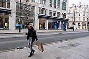 Woman with a Zara bag on Oxford Street which is largely empty of shoppers as the national coronavirus lockdown three continues on 28th January 2021 in London, United Kingdom. Following the surge in cases over the Winter including a new UK variant of Covid-19, this nationwide lockdown advises all citizens to follow the message to stay at home, protect the NHS and save lives. Fashion retailer Zara has been operating a click and collect service.