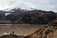 A man stands beside his tent along the shores of Mageik Lake in the Valley of Ten Thousand Smokes, Alaska