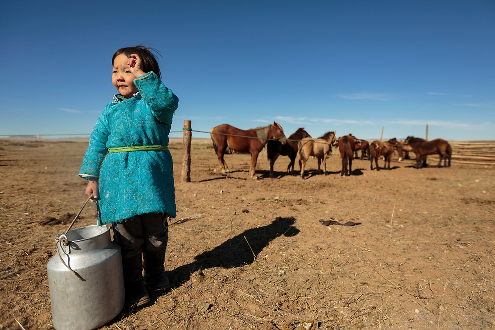 Delgr Tuya is six years old. When she is not at school, she helps with the family chores, carrying the milk back to the nearby ger tent.
