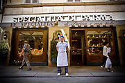 A deli worker stands in front of a speacialty store in Parma Italy