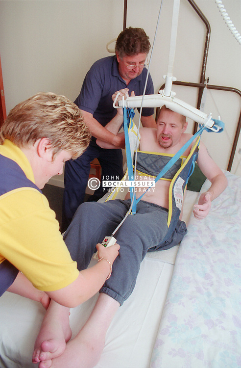 Carers using ceiling hoist to assist wheelchair user to transfer onto bed,