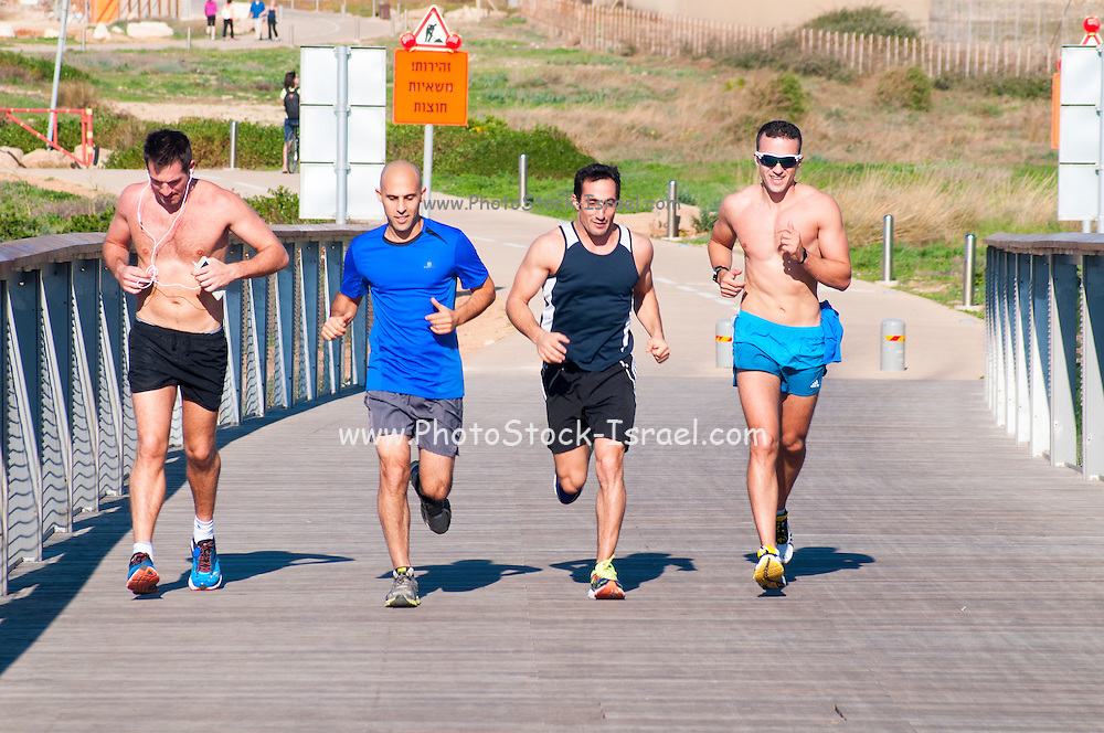 Four young men jog in a park. Photographed in Tel Aviv, Israel
