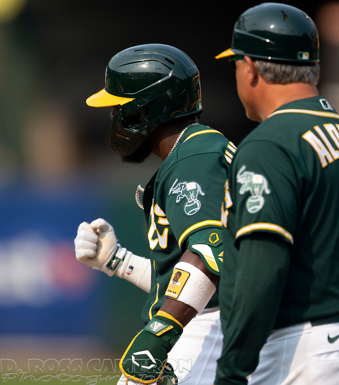 Sep 25, 2021; Oakland, California, USA; Oakland Athletics second baseman Josh Harrison (1) reacts after driving in the tying run against the Houston Astros during the seventh inning at RingCentral Coliseum. First base coach is Mike Aldrete. Mandatory Credit: D. Ross Cameron-USA TODAY Sports