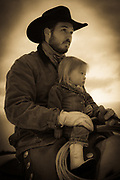 A cowboy and his daughter on horseback at ranch in northeastern Wyoming