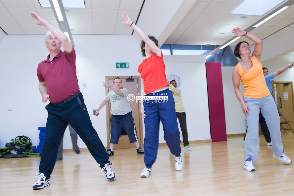 Group of adults taking part in aerobics class at sports leisure centre,