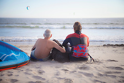 Rear view of kite surfer with his father sitting on the beach, Viana do Castelo, Norte Region, Portugal
