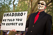 """22 OCTOBER 2011 - PHOENIX, AZ:    An Occupy Phoenix protester with a Guy Fawkes mask stands across the street from a bank in Phoenix Saturday. The demonstrations at Occupy Phoenix, AZ, entered their second week Saturday. About 50 people are staying in Cesar Chavez Plaza, in the heart of downtown. The crowd grows in the evening and on weekends. Protesters have coordinated their actions with police and have gotten permission from the city to set up shade shelters and sleep in the park, but without tents or sleeping bags, which is considered """"urban camping,"""" instead protesters are sleeping on the sidewalk.      PHOTO BY JACK KURTZ"""