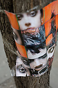 A cellotaped poster of faces and eyes attached to an urban tree in the West End, on 7th March 2019, in London, England.