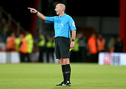 Referee Mike Dean gestures for players to break up the clash during the match