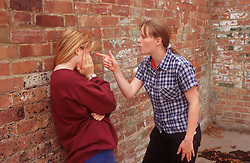 Two teenage girls standing in street arguing; one girl shielding face; one pointing aggressively,
