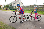 Polish children ages 8 and 4 biking to town wearing helmets. Zawady Central Poland