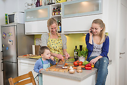 Mother and son grating vegetables while daughter talking on phone