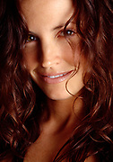 Wavy hair covering part of a woman's happy face in close up.