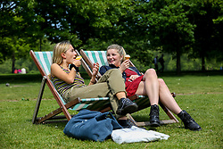 © Licensed to London News Pictures. 15/05/2019. London, UK. Anna (L) and Josie (R) eating ice cream in London's Hyde Park on a warm and sunny day in the capital. Temperatures are set to reach 20C in the capital and potentially higher in the some parts of the UK. Photo credit: Dinendra Haria/LNP