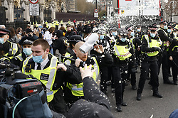 © Licensed to London News Pictures. 03/04/2021. London, UK. A beer can is thrown at police as scuffles break out in Parliament Square during a Kill the Bill demonstration in central London. A coalition of groups including Extinction Rebellion, Kill the Bill & Black Lives Matter are coming together over the Easter weekend to campaign against the proposed Police, Crime, Sentencing and Courts Bill which will give police in England and Wales more power to impose conditions on non-violent protests. Photo credit: Peter Macdiarmid/LNP