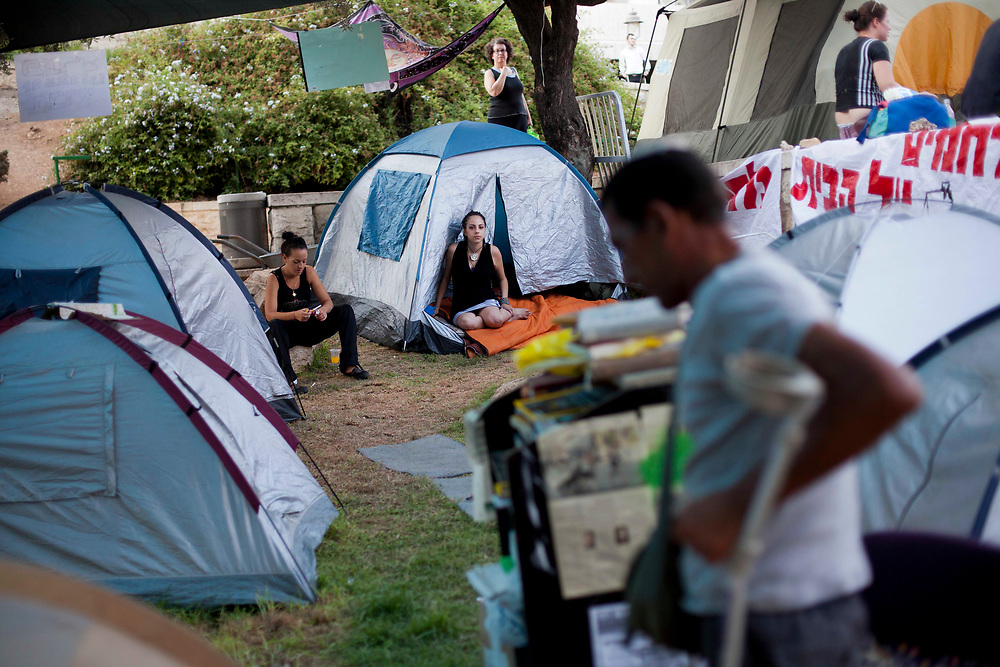 Israelis are seen at a protest tent camp set up in central Jerusalem to call for lower housing and property prices in Israel on August 1, 2011. Over the past three weeks, Israelis have set up tent camps in cities throughout the country, and organized protest marches and demonstrations against social inequalities and the high cost of living.