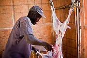 30 OCTOBER 2010 - PHOENIX, AZ: GUMAA BOSSN, who came to the US as refugee from Sudan, butchers a goat at the Goat Meat Store, owned by Ibrahim Swara-Dahab, in Phoenix, AZ. Swara-Dahab came to the United States from Somalia in 1998. He has built a thriving business as a Halal butcher and provides freshly butchered goats and sheep killed following the precepts of Muslim tradition. His business not only caters to Muslims in the Phoenix area but also to refugees and immigrants from Africa and Asia. His small butcher shop is on the Gila River Indian Reservation, about 100 yards from the Phoenix city limits and doesn't have either running water or electricity.    Photo by Jack Kurtz