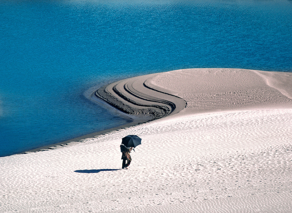 A woman shields herself with a parasol while walking along the Indus River in Pakistan's Khyber Pakhtunkhwa.
