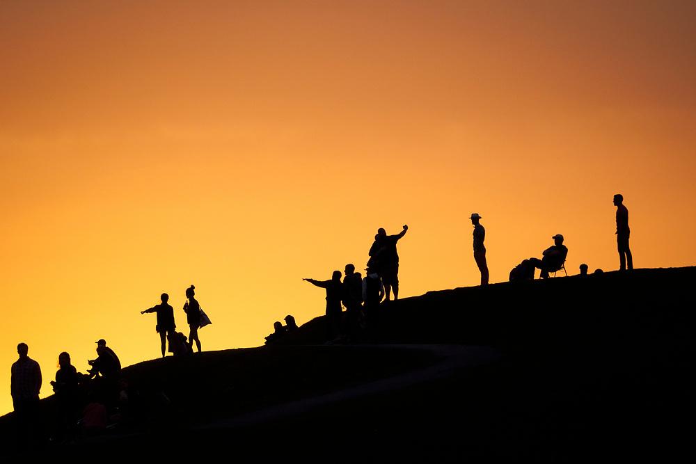 United States, Washington, Seattle. Sunset light silhouettes a variety of people on the hillside at Gasworks Park, Seattle, Washington.
