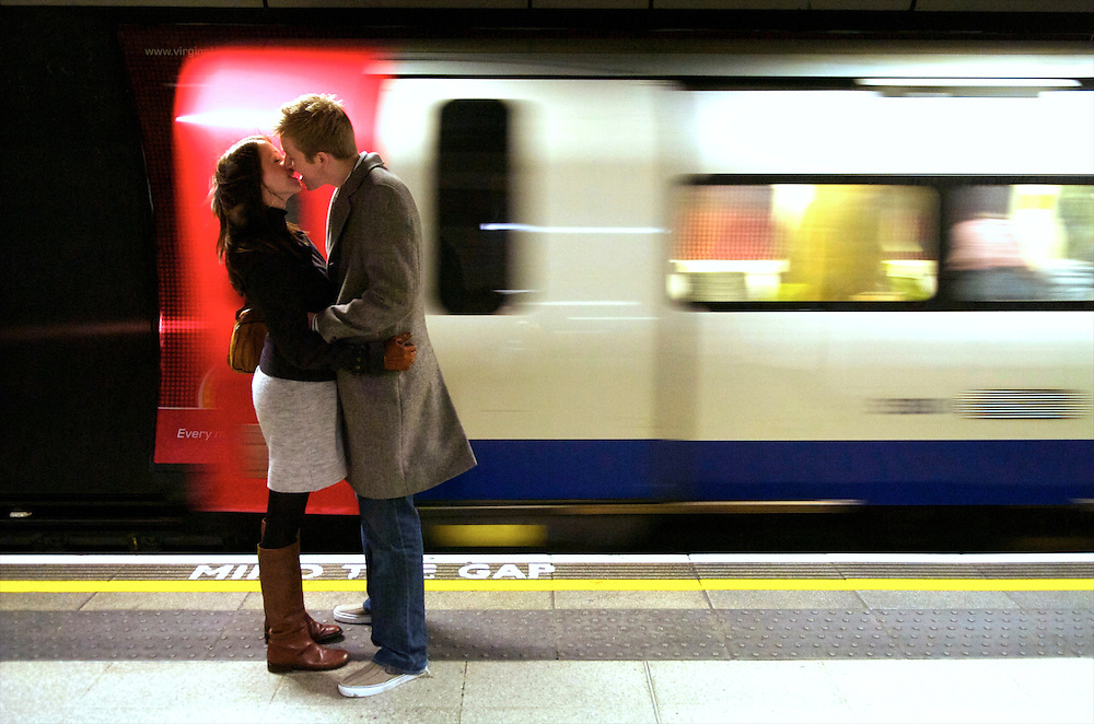 A couple kisses, missing their tube at London Bridge station.  The London Underground is the oldest subway in the world, carrying one billion passengers annually.