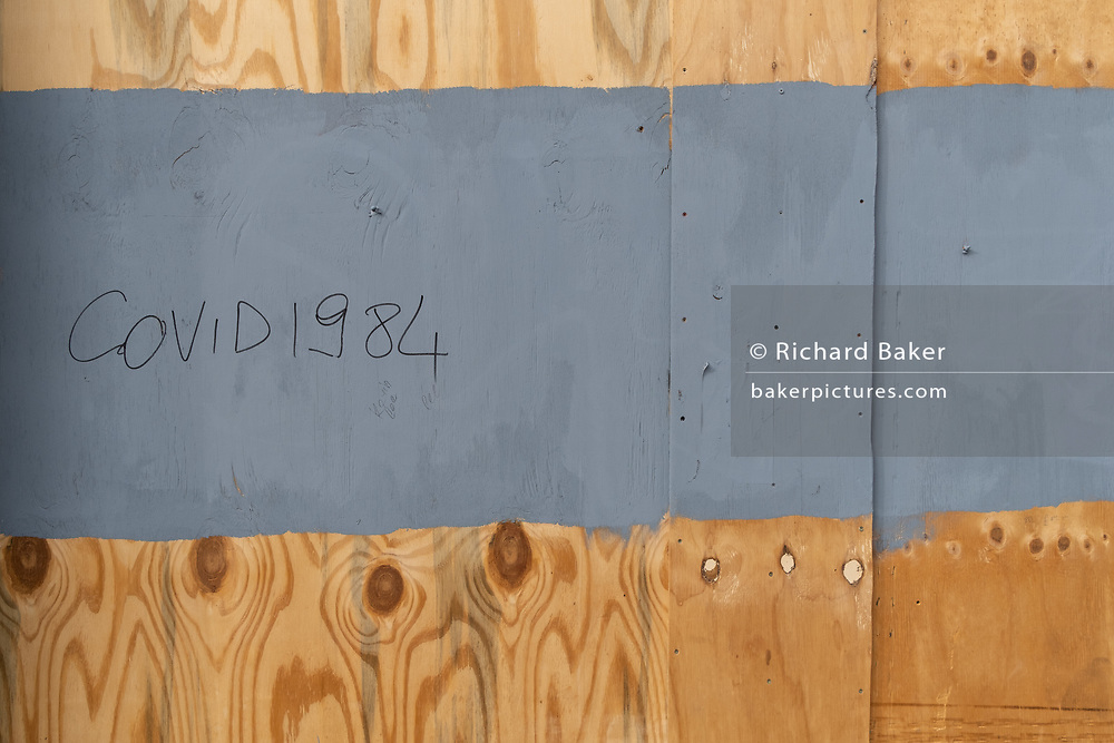 On a plyboard hoarding that has sealed up a Restaurant in Leicester Square, some graffiti suggests that the Coronavirus pandemic is a conspiracy reminiscent of George Orwell's cult dystopian work, '1984', on 29th September 2020, in London, Westminster, England.