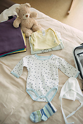 Still life baby clothes bed teddy bear packing