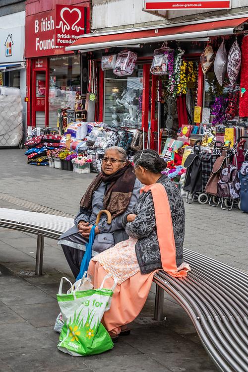Two elderly Indian women sitting chatting. High Street, West Bromwich, West Midlands, UK.
