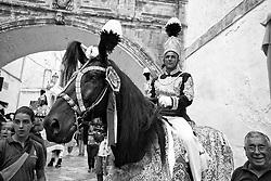 Ostuni Cavalcata S.Oronzo agosto 2012. Cavaliere a cavallo con i finimenti e pennacchio, con la folla intorno e arco da cornice..Sant'Oronzo si nascose anche in una grotta a Ostuni, nel luogo dove è stata poi costruita la chiesa e il relativo Santuario. I festeggiamenti si svolgono nella Città Bianca il 25, 26 e 27 agosto con la rinomata Cavalcata di Sant'Oronzo, una processione nella quale sfilano esponenti del clero e dell'amministrazione comunale, seguiti da cavalli e cavalieri, con stoffe rosse ricche di ricami e lustrini. I festeggiamenti comprendono anche due fiere e uno spettacolo di fuochi.