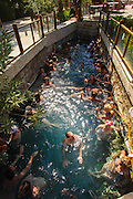 The Sacred pool packed with tourists at Hierapolis, the roman ruins at the top of Pamukkale hill.  Those who want to enjoy the thermal waters, can take a dip in the pool, littered with fragments of marble pillars. The hard, white mineral deposits of Pamukkale, which from a distance resemble snow, are caused by the high mineral content of the natural spring water which runs down the cliff and congregates in warm pools on the terraces. This is such a popular tourist attraction that strict rules had to be established in order to preserve its beauty, which include the fact that visitors may no longer walk on the terraces.