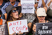 24 MAY 2014 - BANGKOK, THAILAND: Women hold up a signs against the Thai junta at a shopping mall in Bangkok. There were several marches in different parts of Bangkok to protest the coup that unseated the popularly elected government. Soldiers and police confronted protestors and made several arrests but most of the protests were peaceful. The military junta also announced that firing of several police commanders and dissolution of the Thai Senate. The junta also changed its name from National Peace and Order Maintaining Council (NPOMC) to the National Council for Peace and Order (NCPO).   PHOTO BY JACK KURTZ