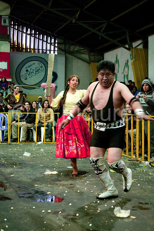 Alicia Flores female wrestler chasing male opponent with a wooden plank, out of ring with crowd in background. Lucha Libre wrestling origniated in Mexico, but is popular in other latin Amercian countries, including in La Paz / El Alto, Bolivia. Male and female fighters participate in the theatrical staged fights to an adoring crowd of locals and foreigners alike.
