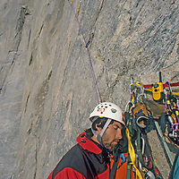 Mountaineer Mark Synnott dozes during a ten hour belay as Alex Lowe leads extreme aid climbing on Great Sail Peak, an Arctic big-wall rock climb on Canada's Baffin Island. (An automatic belay device would catch a fall).