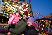A young family enjoys their time at the carnival during the Fur Rondy Festival, downtown Anchorage.