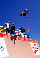 1998:  National Inline Skate Series Championships (NISS) vert ramp skater catches big air on his roller skates. Vintage skating competition photo.