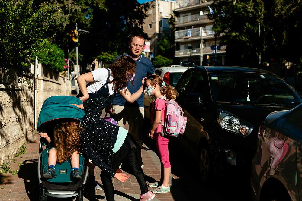 Anna Michel adjusts her daughters, Clil's, hair as her twin Alma plays with their brother Ofek, and father Matti Michel watches, during their walk towards the elementary school where the girls study, in Jerusalem, Israel, on May 3, 2020.