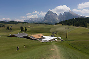 Hiker on the Siusi plateau, above the South Tyrolean town of Ortisei-Sankt Ulrich in the Dolomites, Italy.