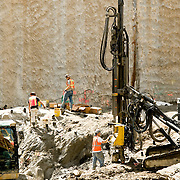 Construction workers in large pit with pit drilling machine.